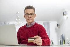 Homem maduro que usa o cartão e o portátil de crédito para comprar em linha em casa Imagens de Stock Royalty Free