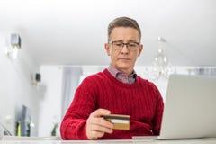 Homem maduro que usa o cartão e o portátil de crédito para comprar em linha em casa Foto de Stock Royalty Free