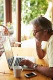 Homem maduro que usa o portátil na cozinha Fotografia de Stock Royalty Free