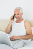Homem maduro que usa o telefone celular e o portátil na cama Fotos de Stock