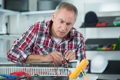Homem maduro que verifica a edição do radiador com a ferramenta do multímetro imagem de stock royalty free