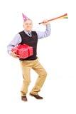 Homem maduro que veste um chapéu do partido e que guardara um presente imagens de stock royalty free