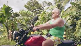 Homem maduro que viaja na motocicleta no campo tropical em montes verdes e em paisagem da floresta úmida Homem s?nior video estoque
