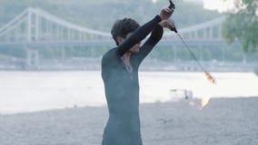 Homem magro do retrato que executa uma mostra com a posição do fã do fogo no riverbank na frente das árvores Artista hábil do fir filme