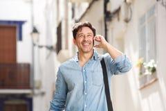 Homem mais idoso alegre que anda fora e que faz um telefonema imagens de stock royalty free