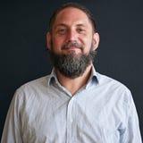 Homem mais idoso com a barba que olha em linha reta na câmera ao sorrir Imagem de Stock