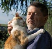 Homem mais idoso com um gato Fotos de Stock Royalty Free