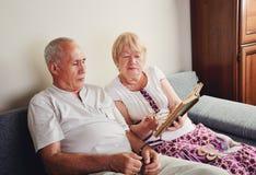 Homem mais idoso e mulher 60-65 anos de assento velho no sofá e lido Foto de Stock