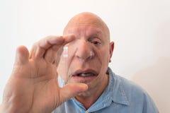 Homem mais idoso que olha sobre uma grande lente, distorção, calva, calvície, quimioterapia, câncer, no branco imagens de stock royalty free