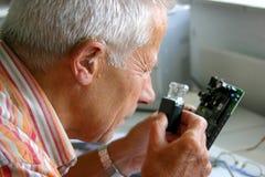 Homem mais idoso que tenta ler as letras minúsculas no printboard imagens de stock royalty free