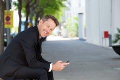 Homem mais idoso seguro que guarda o telefone celular que senta-se fora foto de stock royalty free