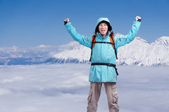 Homem masculino feliz do alpinista com braços aumentados Em montanhas altas do fundo acima das nuvens Fotos de Stock Royalty Free