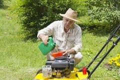 Homem meados de da idade que adiciona o petróleo ao lawnmover fotografia de stock