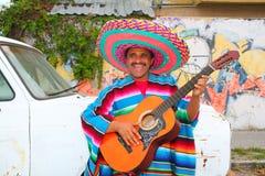 Homem mexicano do humor que sorri jogando o sombrero da guitarra Foto de Stock Royalty Free