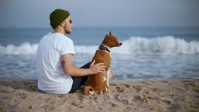 Homem milenar novo com o cão do melhor amigo na praia vídeos de arquivo
