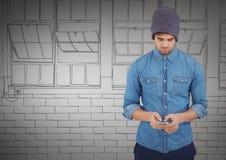 Homem milenar que texting contra mão cinzenta janelas tiradas Fotografia de Stock Royalty Free