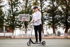 Homem moderno no equipamento preto e branco à moda que monta o 'trotinette' elétrico na cidade fotos de stock