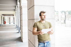 Homem moderno ocasional com o tablet pc na rua que olha afastado fotos de stock