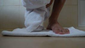 Homem molhado que pisa fora do banho na toalha, limpando os pés, prevenção do fungo do prego video estoque