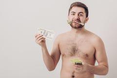 Homem moreno considerável novo com barba que come cem notas de dólar dinheiro e avidez Fotografia de Stock Royalty Free