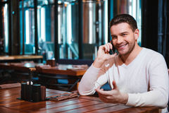 Homem moreno positivo que põe seu telefone celular à orelha Fotos de Stock