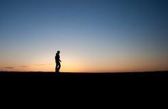 Homem mostrado em silhueta no por do sol Imagem de Stock