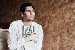Homem muçulmano árabe com o livro sagrado do koran com rosário imagem de stock
