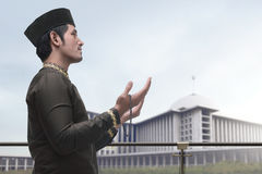 Homem muçulmano asiático religioso no vestido do traidional que reza ao deus fotografia de stock