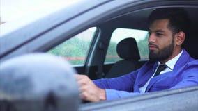 Homem muçulmano no terno azul que conduz o carro Homem de negócios sério considerável vídeos de arquivo