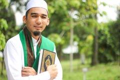 Homem muçulmano que guarda o Al-Corão Foto de Stock