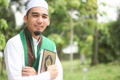 Homem muçulmano que guarda o Al-Corão Fotografia de Stock Royalty Free
