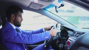 Homem muçulmano que senta-se no assento do ` s do motorista no carro e que datilografa no smartphone video estoque