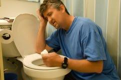 Homem muito doente que joga acima no toalete Foto de Stock