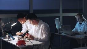 Homem multirracial e mulher que verificam o cartão-matriz com o verificador do multímetro no laboratório de eletrônica filme