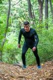 Homem muscular ativo novo no sportswear que corre através do passeio na natureza na floresta para a cardio- imagem do vertical do foto de stock
