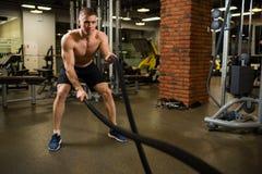 Homem muscular atlético contratado com uma corda grossa com um torso desencapado no gym fotografia de stock royalty free