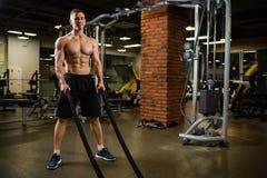 Homem muscular atlético contratado com uma corda grossa com um torso desencapado no gym imagens de stock
