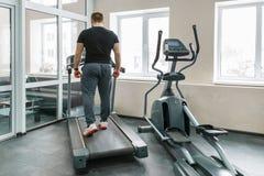 Homem muscular atlético que corre em escadas rolantes no gym moderno do esporte Aptidão, esporte, treinamento, conceito dos povos fotos de stock