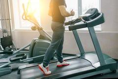 Homem muscular atlético que corre em escadas rolantes no gym moderno do esporte Aptidão, esporte, treinamento, conceito dos povos foto de stock