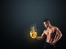 Homem muscular com dumbbells no fundo preto Fotografia de Stock Royalty Free