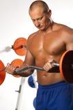 Homem muscular com pesos de uma barra na formação das mãos Fotografia de Stock
