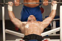 Homem muscular com pesos de uma barra na formação das mãos imagem de stock