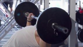 Homem muscular considerável que faz a imprensa de banco no gym vídeos de arquivo