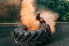 Homem muscular considerável que lança o pneu grande exterior foto de stock royalty free