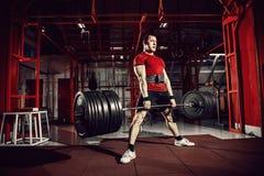 Homem muscular da aptidão que faz o deadlift um barbell no fitness center moderno Treinamento funcional imagem de stock royalty free