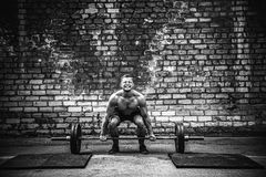 Homem muscular da aptidão que faz o deadlift um barbell sobre sua cabeça em exterior, gym da rua Treinamento funcional fotografia de stock royalty free