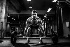 Homem muscular da aptidão que faz o deadlift um barbell sobre sua cabeça no fitness center moderno Treinamento funcional foto de stock royalty free