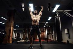 Homem muscular da aptidão que faz o deadlift um barbell sobre sua cabeça no fitness center moderno Treinamento funcional fotos de stock royalty free