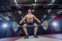 Homem muscular da aptidão que prepara ao deadlift um barbell sobre sua cabeça no fitness center moderno Treinamento funcional sna fotos de stock