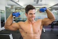 Homem muscular descamisado que dobra os músculos no gym Fotos de Stock